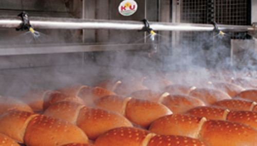 A Lechler pneumatic atomizing nozzle, such as the AirMist, can be used to apply water to prevent dehydration in foods. The AirMist combines air and liquid to create very fine droplets that produce a light mist required for applications such as in this bakery. Source: Lechler